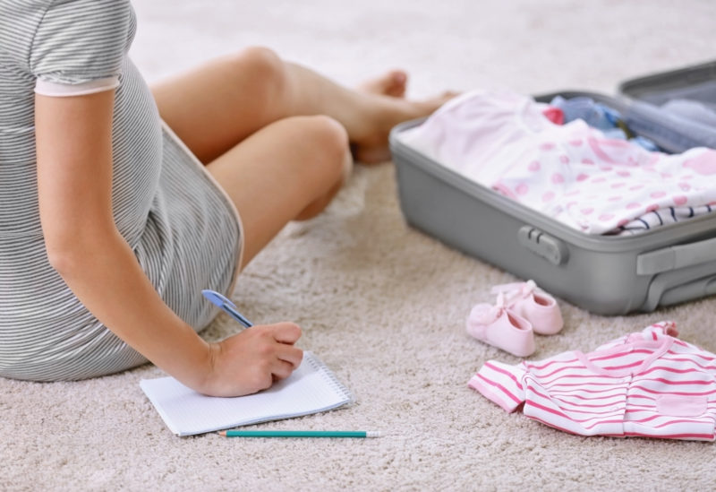 Things to Do Before You Give Birth; Pregnant woman packing suitcase for maternity hospital at home
